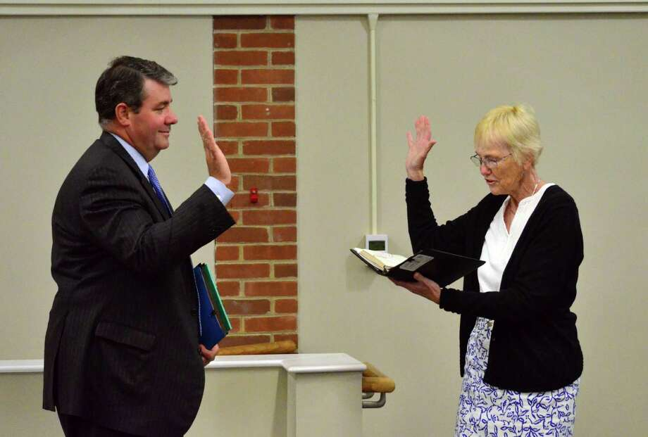 "Town Clerk Donna Rajczewski, right, swore in new Board of Education member David ""Duke"" Dineen on Tuesday night. Photo: Megan Spicer / Darien News"
