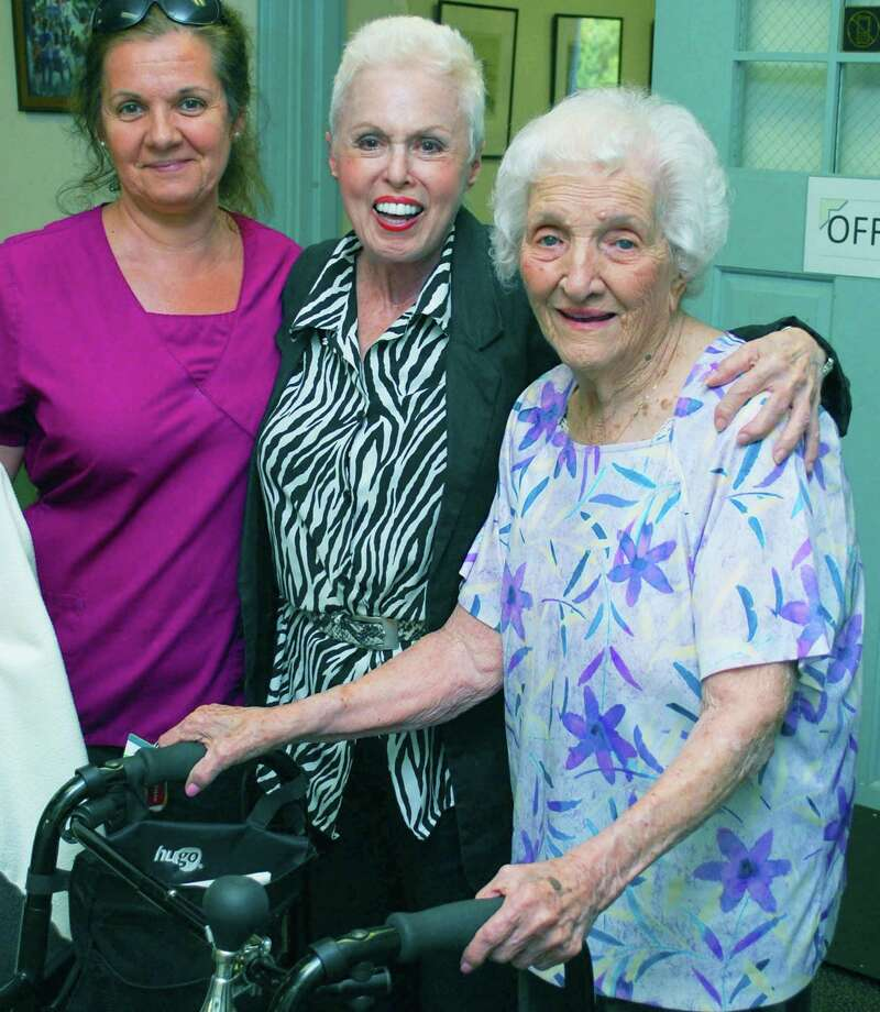 Members of the New Milford Senior Center must check in upon arrival at the Main Street facility. Above, Dorothea Cosentino, right, joins her CNA Maria Pereira, left, and center receptionist Maxine Hayes for a photograph before meeting friends.  For Spectrum Maturity 2014. Photo: Deborah Rose / The News-Times