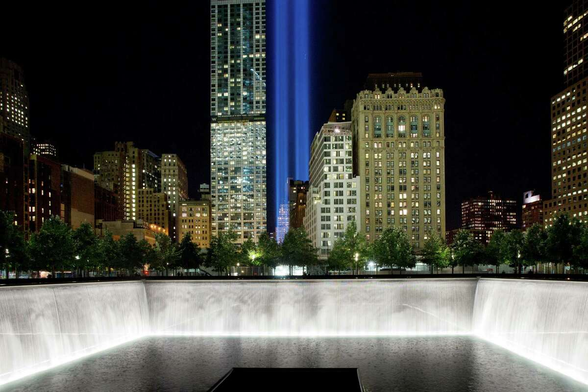 The Tribute in Light rises behind buildings adjacent to the 1 World Trade Center and a reflecting pool at the National September 11 Memorial, Monday, Sept. 8, 2014, in New York. The tribute, an art installation of 88 searchlights aiming skyward in two columns, is a remembrance of the Sept. 11, 2001, attacks. (AP Photo/Mark Lennihan)