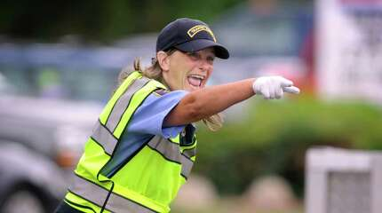 Kat Holick, 47, of the Sandy Hook section of Newtown, Conn., is a traffic agent, directing traffic at the entrance to schools in Newtown, Tuesday, Sept. 9, 2014.