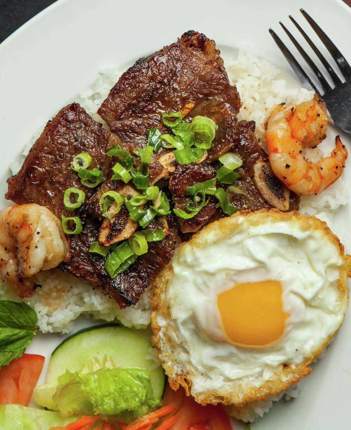 Interior of Huynh Restaurant Authentic Vietnamese Cuisine's Com Suon Bo Dai Han, chargrilled beef, short ribs served with shrimp, fried egg and crushed rice. Photographed, Monday, August 4, 2014, in Houston. ( Nick de la Torre )