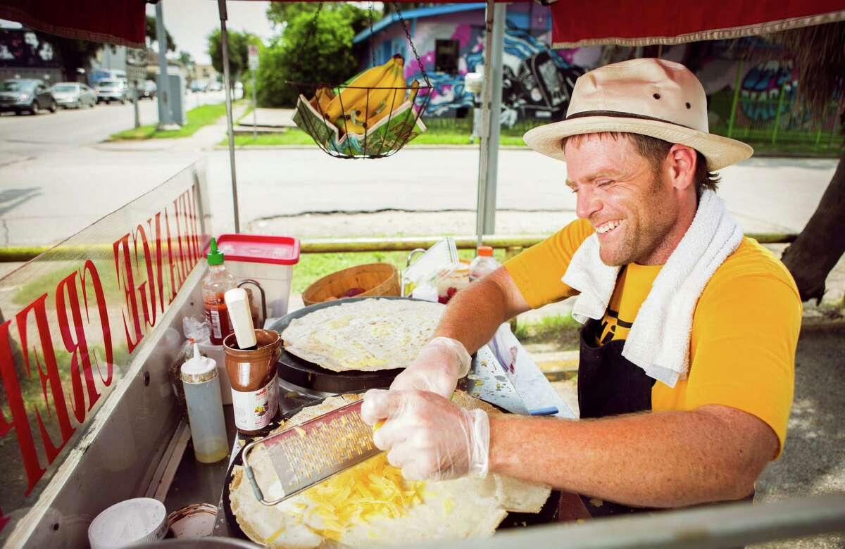 FOR CHRON 100 RESTAURANT REVIEW. DO NOT USE FOR ANYTHING ELSE WITHOUT A PHOTO EDITOR'S PERMISSION. THANKS. Sean Carroll, owner of Melange Creperie, jokes with customers as he shreds cheese on a crepe on his crepe cart, photographed, Sunday, July 20, 2014, in Houston. ( Nick de la Torre )