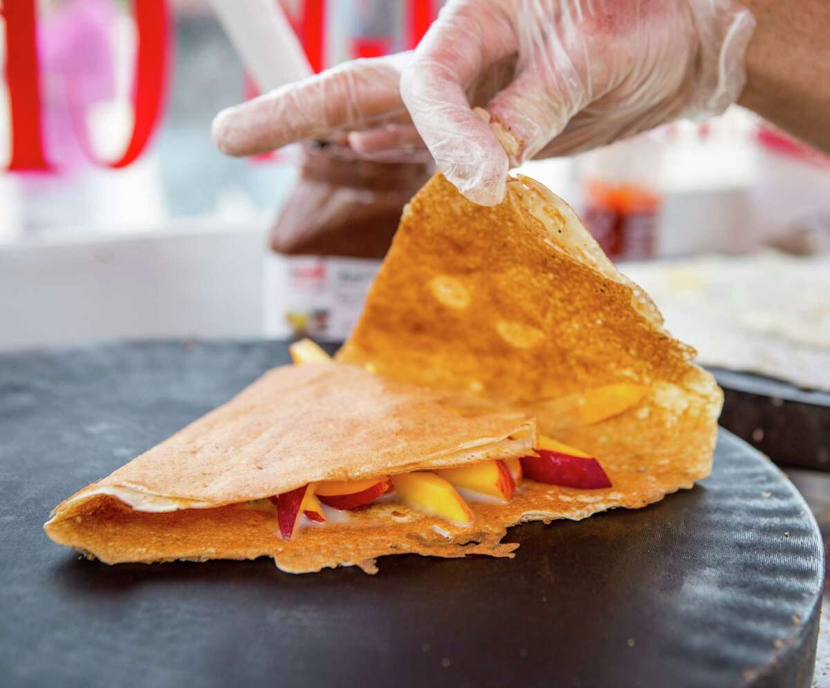Sean Carroll, owner of Melange Creperie, folds a nectarine crepe at his mobil creperie, photographed, Sunday, July 20, 2014, in Houston. ( Nick de la Torre )