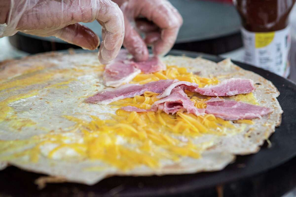 Sean Carroll, owner of Melange Creperie, places ham on an egg, ham and cheese crepe, Sunday, July 20, 2014, in Houston. ( Nick de la Torre )