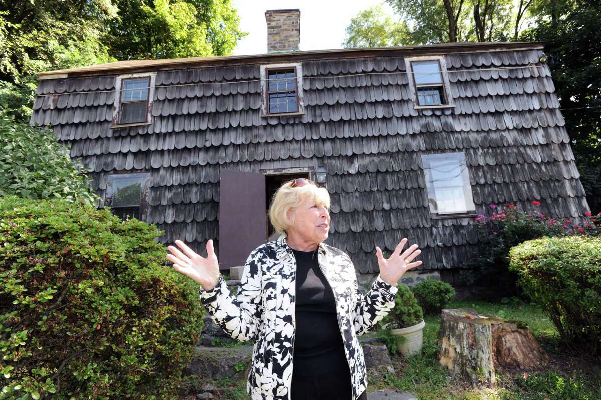 """Jo Conboy, of the Greenwich Preservation Trust, in front of the Thomas Lyon House at 1 Byram Road, Greenwich, Conn., Wednesday, Sept. 10, 2014. The house was the Lyon family homestead as well as the one-time home of Peter John Lee, a fugitive slave, who worked for Seth Lyon in the 1830s. In 1836, Lee was abducted by """"blackbirders"""" across the Byram Bridge, in New York state, and taken back to the south."""