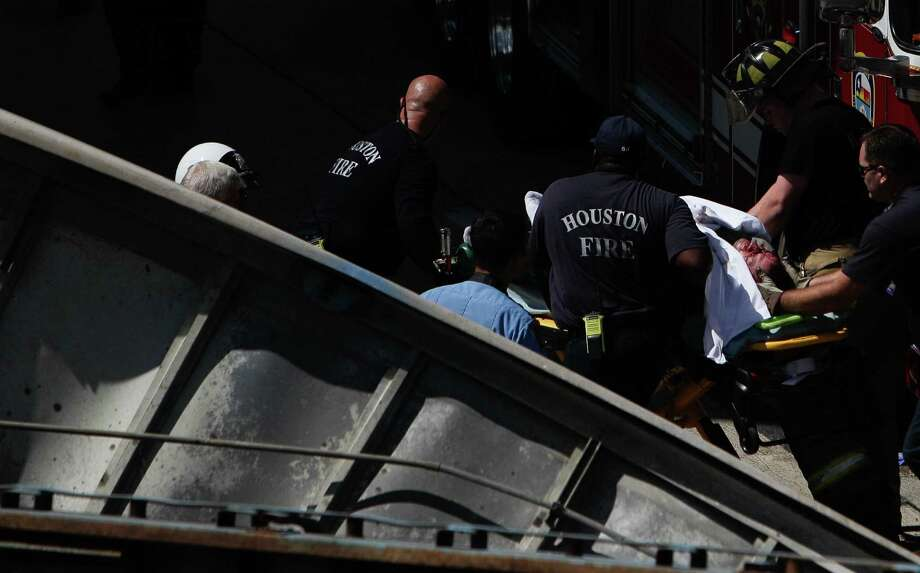 Emergency crews rescue the driver after his big-rig plunged off an overpass onto the Eastex Freeway about 10:30 a.m. Wednesday. Officials initially reported that the driver had died, but later determined he sustained non-life-threatening injuries. Photo: Mayra Beltran / Houston Chronicle
