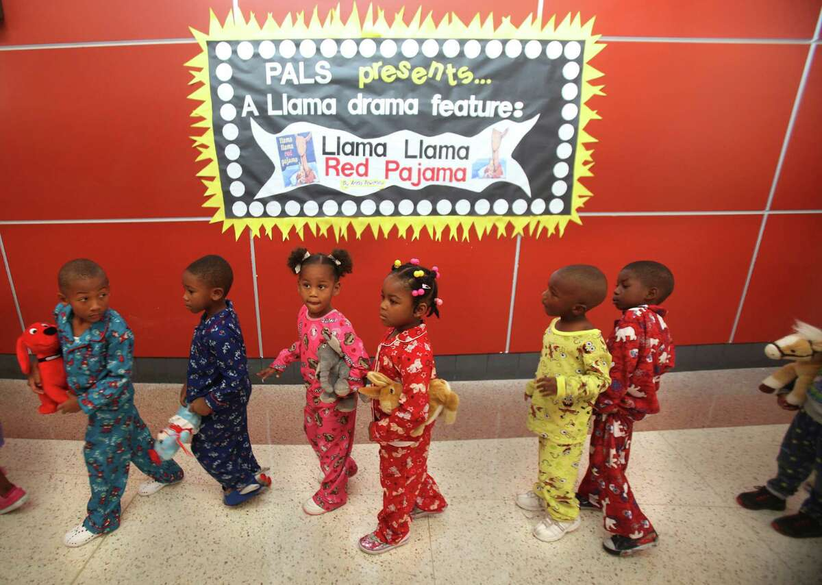 """Pre-Kindergarden students walk to the library to participate in setting a world reading record by reading their favorite book """"Llama Llama Red Pajama"""" in their pajama's at Thompson Elementary School on Thursday, Oct. 6, 2011, in Houston. The students at HISD and across the country will """"read for the record"""" as part of a major effort promoted by the Pearson Foundation to raise awareness for the need to read to children at the youngest ages. For the first time ever, children nationwide will also attempt to break the record for the largest number of children being read to from a digital story online. ( Mayra Beltran / Houston Chronicle )"""