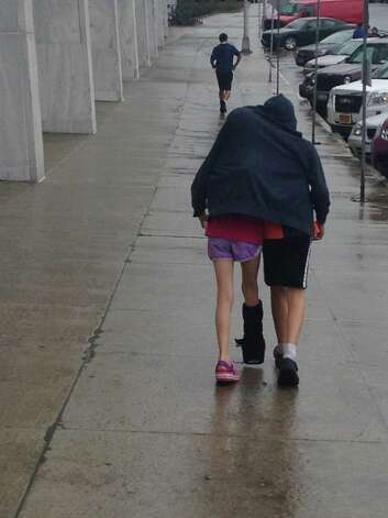 Brother takes care of sister as they leave the State Museum in Albany in the rain earlie this month. (Randy and Heather Voges of Clifton Park)