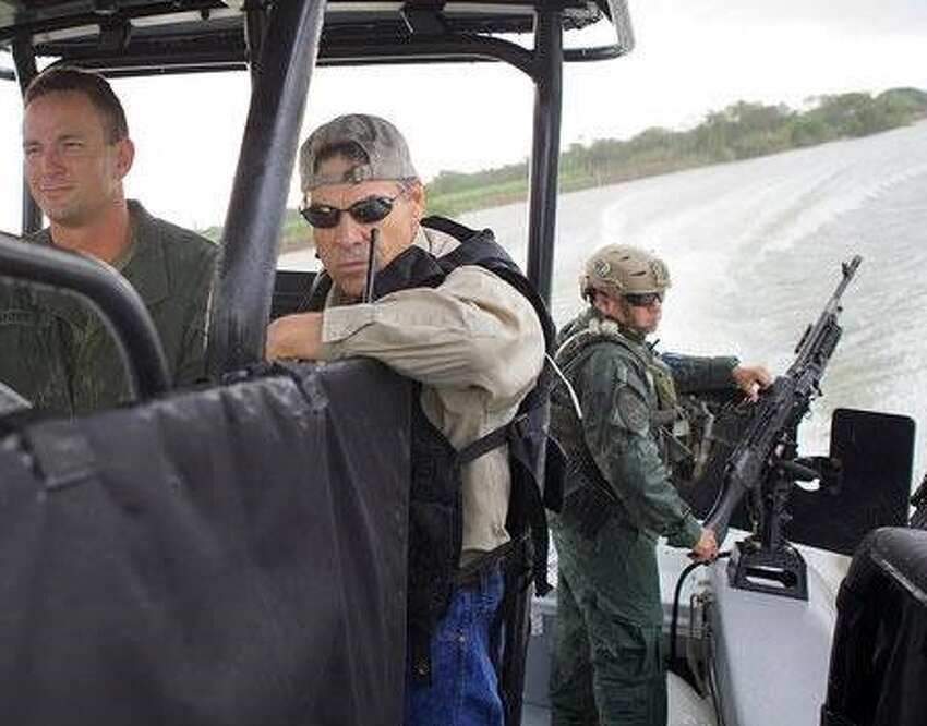 Gov. Rick Perry poses for a photo op on a Department of Public Safety gun boat during a July 2014 trip to the border.