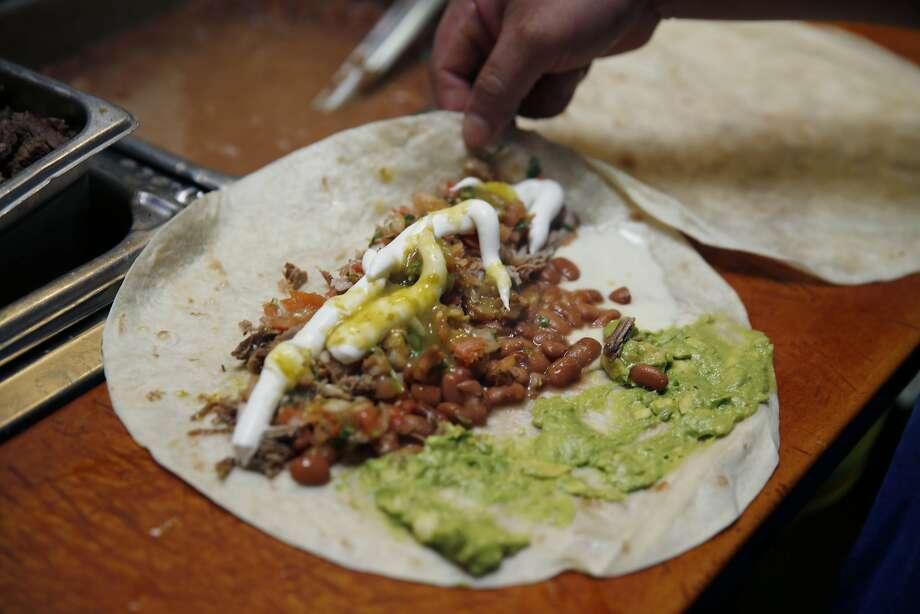 Salomon Gonzalez makes a carnitas super burrito at  La Taqueria on Wednesday, September 10,  2014 in San Francisco, Calif. Photo: Lea Suzuki, The Chronicle