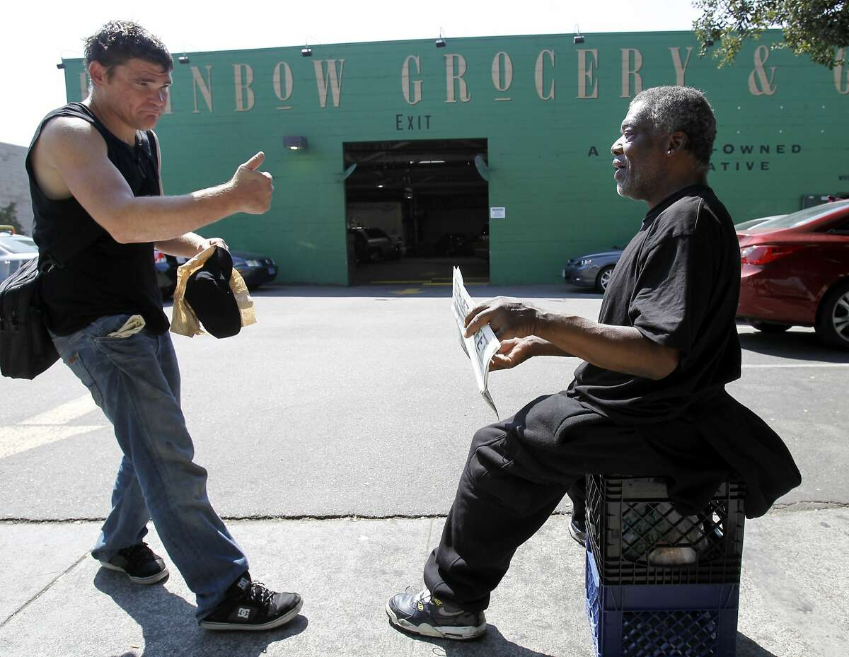 Homeless man Travis Moore (left) stops to share some change with homeless man Reggie White as he sits in front of the Rainbow Grocery Wednesday September 10, 2014 in San Francisco, Calif. The Street Sheet is celebrating the 25 year anniversary of the newspaper.