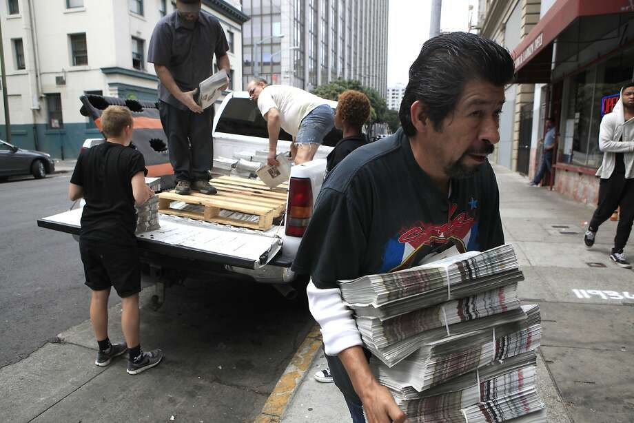 Miguel Carrera, a director with the Coalition on Homelessness that publishes the Street Sheet, carries a stack of papers. Photo: Michael Short, The Chronicle