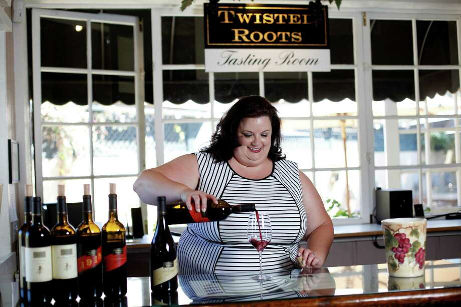 Julie Ruiz pours wine at the Twisted Roots tasting room in Carmel Valley, which she opened with husband Josh Ruiz in 2012. Photo: Sarah Rice / Special To The Chronicle / ONLINE_YES