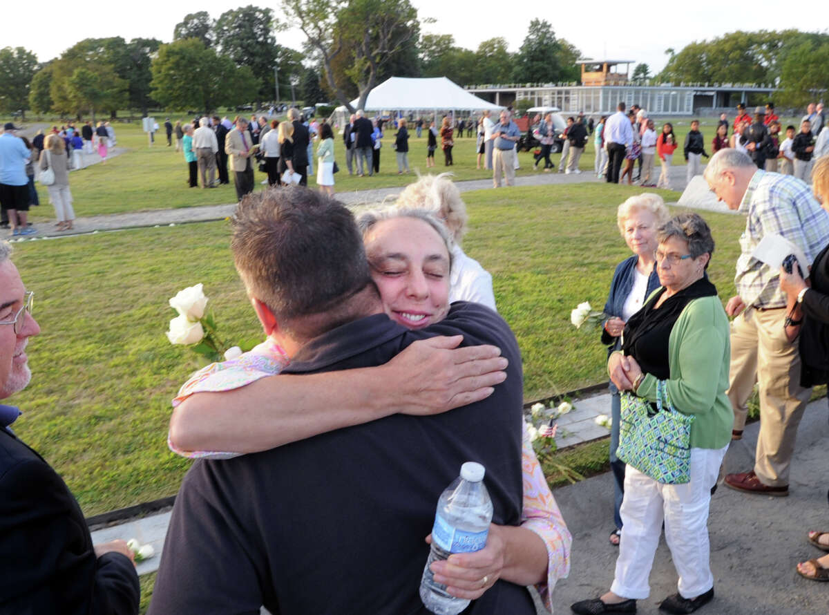 At center, Elizabeth Bullis-Wiese of Fairfield, Conn., hugs a friend during the September 11th Memorial Ceremony remembering the Connecticut victims who were murdered in the terrorist attacks on Sept. 11th, 2001, at Sherwood Island State Park in Westport, Conn., Wednesday night, Sept. 10, 2014. Bullis-Wiese honored her sister, Dianne Bullis Snyder, who was killed during the attack while serving as a flight attendant on American Airlines Flight 11.