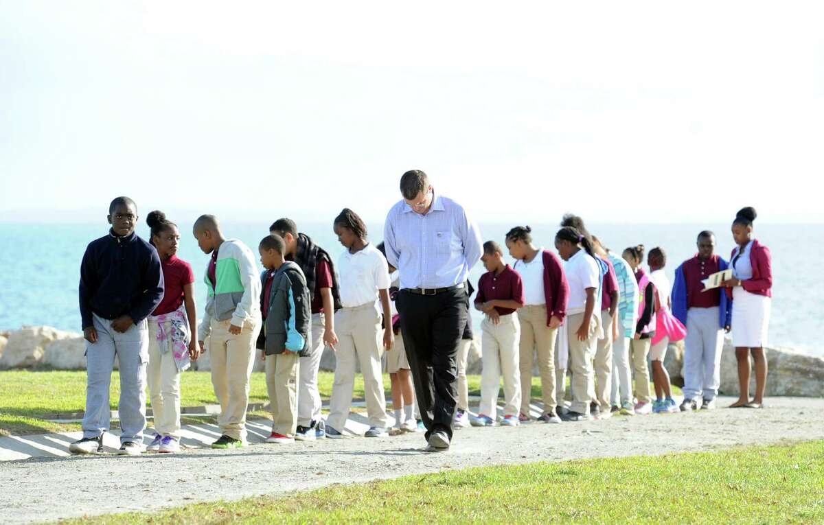 With a bowed head, Ryan Howard , a teacher for the Classical Studies Academy of Bridgeport, with his students during the September 11th Memorial Ceremony remembering the Connecticut victims who were murdered in the terrorist attacks on Sept. 11th, 2001, at Sherwood Island State Park in Westport, Conn., Wednesday night, Sept. 10, 2014.
