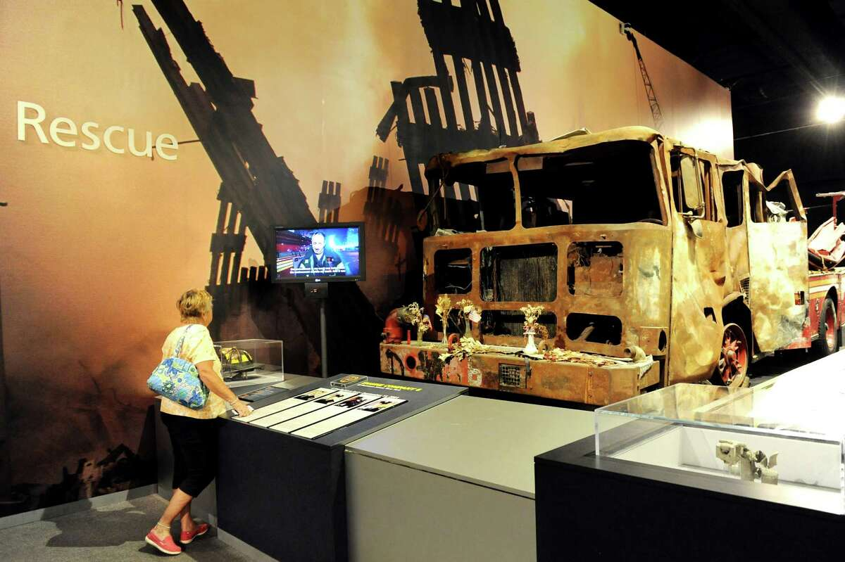 Bonnie Sisco of St. Petersburg, Fla. watches the story of Engine 6 in a looping video at the World Trade Center exhibit on Wednesday, Sept. 10, 2014, at the New York State Museum in Albany, N.Y. Sisco, was visiting family, said her niece witnessed the terrorist attacks. (Cindy Schultz / Times Union)