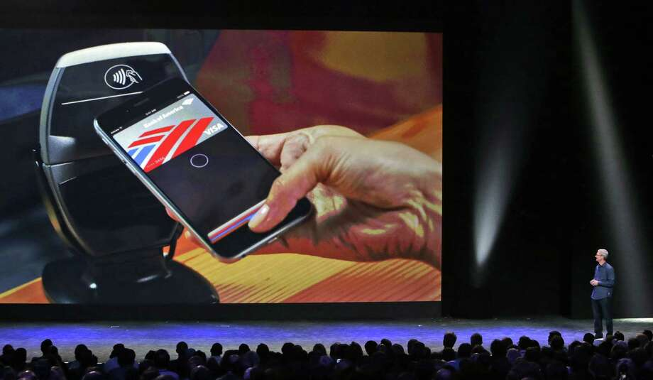 Apple CEO Tim Cook introduces the Apple Pay product Tuesday in Cupertino, Calif. It will be available only on the new smartphones iPhone 6 and the larger iPhone 6 Plus, along with the Apple Watch. Photo: Marcio Jose Sanchez, Associated Press / AP