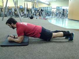 Gold's Gym personal trainer Brandon Carleo shows the proper form for a plank. The plank is an isometric core exercise.