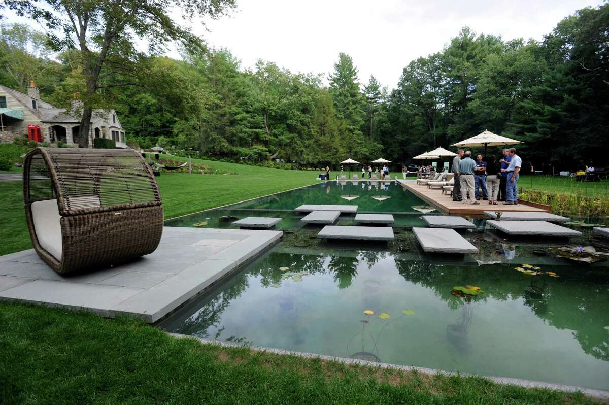 The owners of Freddys Landscape Company unveil a new eco-friendly pool recently completed at a clients home on Taunton Hill Road in Newtown, Conn. It was created out of an existing pond on the site. In the foreground of the photo is a lily pond which is part of the pool.