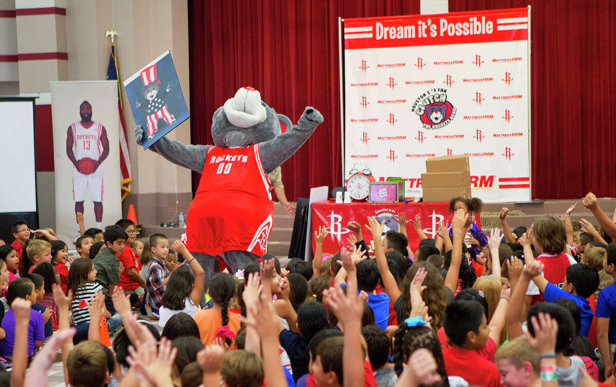 Houston Rockets' mascot, Clutch, shows Gleason Elementary School students a picture of Clutch dressed as the president to remind students they can be whatever they want when they grow up, Wednesday, Sept. 10, 2014, in Houston.
