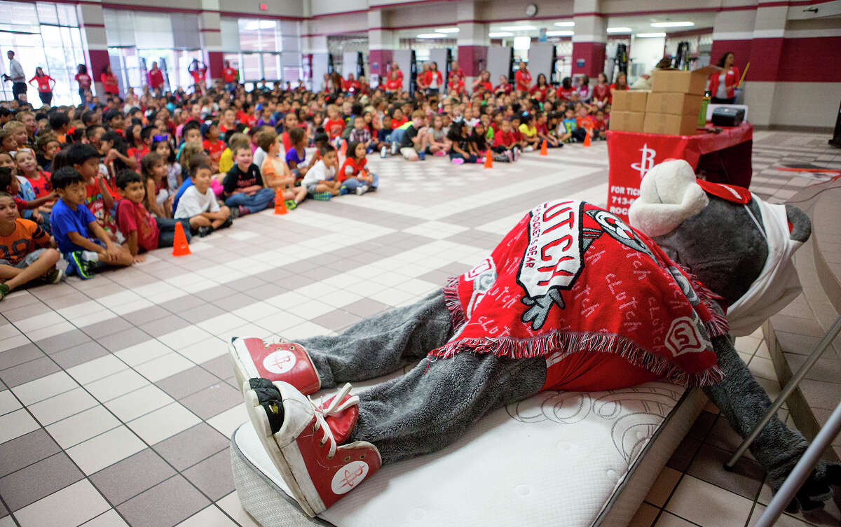 """Gleason Elementary School students watch as the Houston Rockets' mascot, Clutch, takes a nap during a visit to the school, Wednesday, Sept. 10, 2014, in Houston. The visit was part of the """"Good Night Sleep Show"""" tour in an effort to teach children about the importance of a good night's sleep for their education and health. The tour stresses the importance of getting 10 to 12 hours of sleep per night because rest helps with focus and learning."""