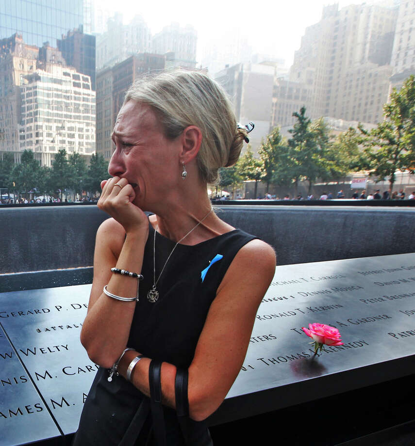 Carrie Bergonia of Pennsylvania looks at the name of her fiance, firefighter Joseph Ogren, at the 9/11 Memorial during last year's ceremony. Photo: Getty Images / File Photo / 2013 Getty Images