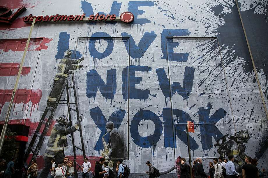 """NEW YORK, NY - SEPTEMBER 10:  New artwork is shown on the side of the Century 21 store near the National September 11 Memorial on September 10, 2014 in New York, United States. The artwork, which shows a fire fighter writing """"We Love New York,"""" is by artist """"Mr. Brainwash,"""" who was featured prominently in the documentary """"Exit through the Gift Shop."""" Tomorrow the country will mark the 13th anniversary of the attacks.  (Photo by Andrew Burton/Getty Images) Photo: Andrew Burton, Getty Images"""