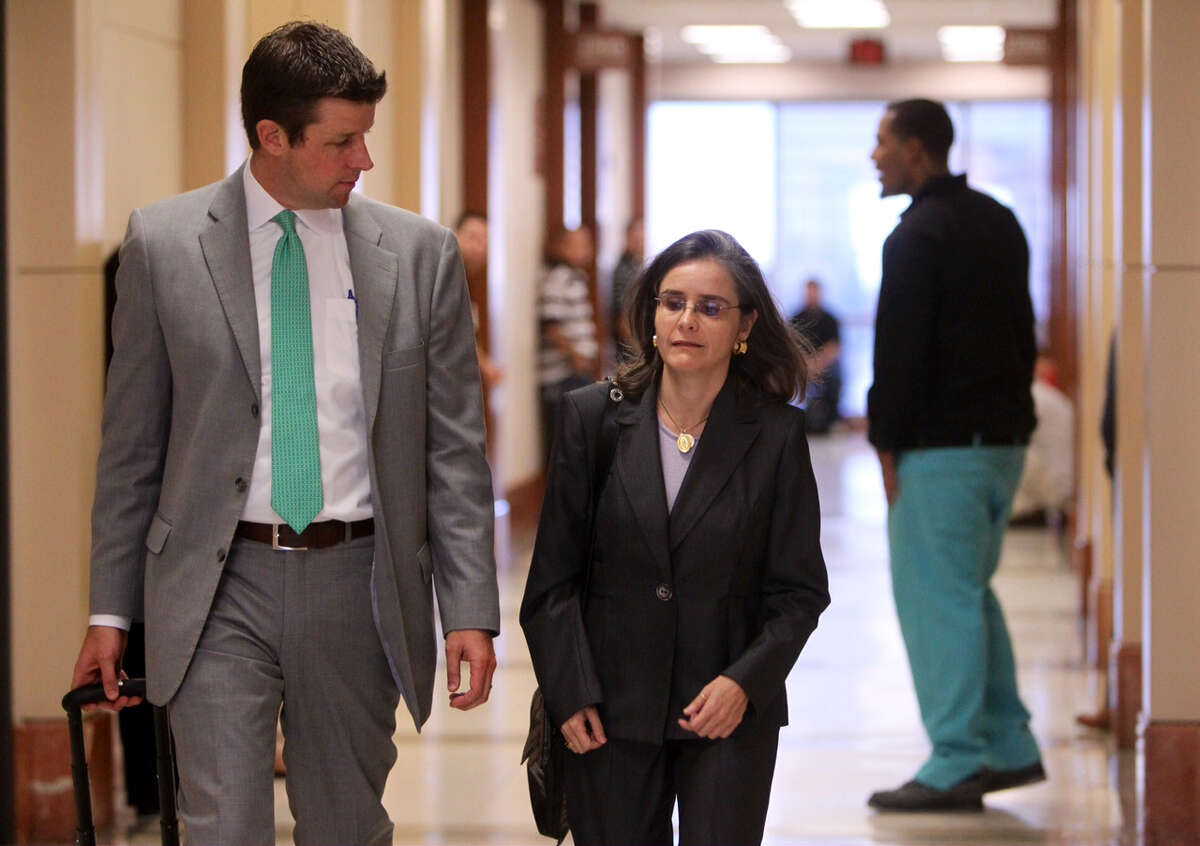 Dr. Ana Maria Gonzalez-Angulo, right, walks into court with attorney Derek Hollingsworth for jury selection in her trial on a felony charge of aggravated assault, Thursday, Sept. 11, 2014. She was charged in May 2013 with poisoning Dr. George Blumenschein.