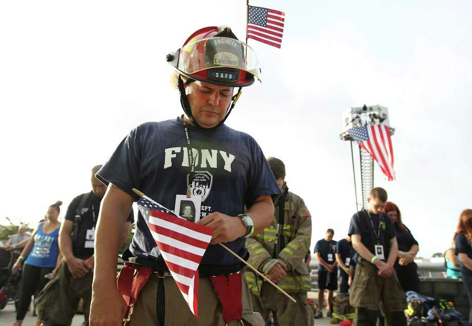 San Antonio Firefighter Gino Montemayor bows in prayer before the San Antonio 110 9/11 Memorial Climb at the Alamodome on Thursday, Sept. 11, 2014. Hundreds of first responders and civilians gathered to take part in the event to pay tribute to the fallen firefighters from Sept. 11, 2001. Each participating first responder carried the face and name of firefighter that perished 13 years ago in New York City. Many wore bunker gear and breathing apparatus that added up to additional pounds as a tribute during their climb. At the end of the climb, a name tag of the fallen firefighter was placed on a 9/11 memorial, their name called out and a bell was rung. Photo: Kin Man Hui, San Antonio Express-News / ©2014 San Antonio Express-News