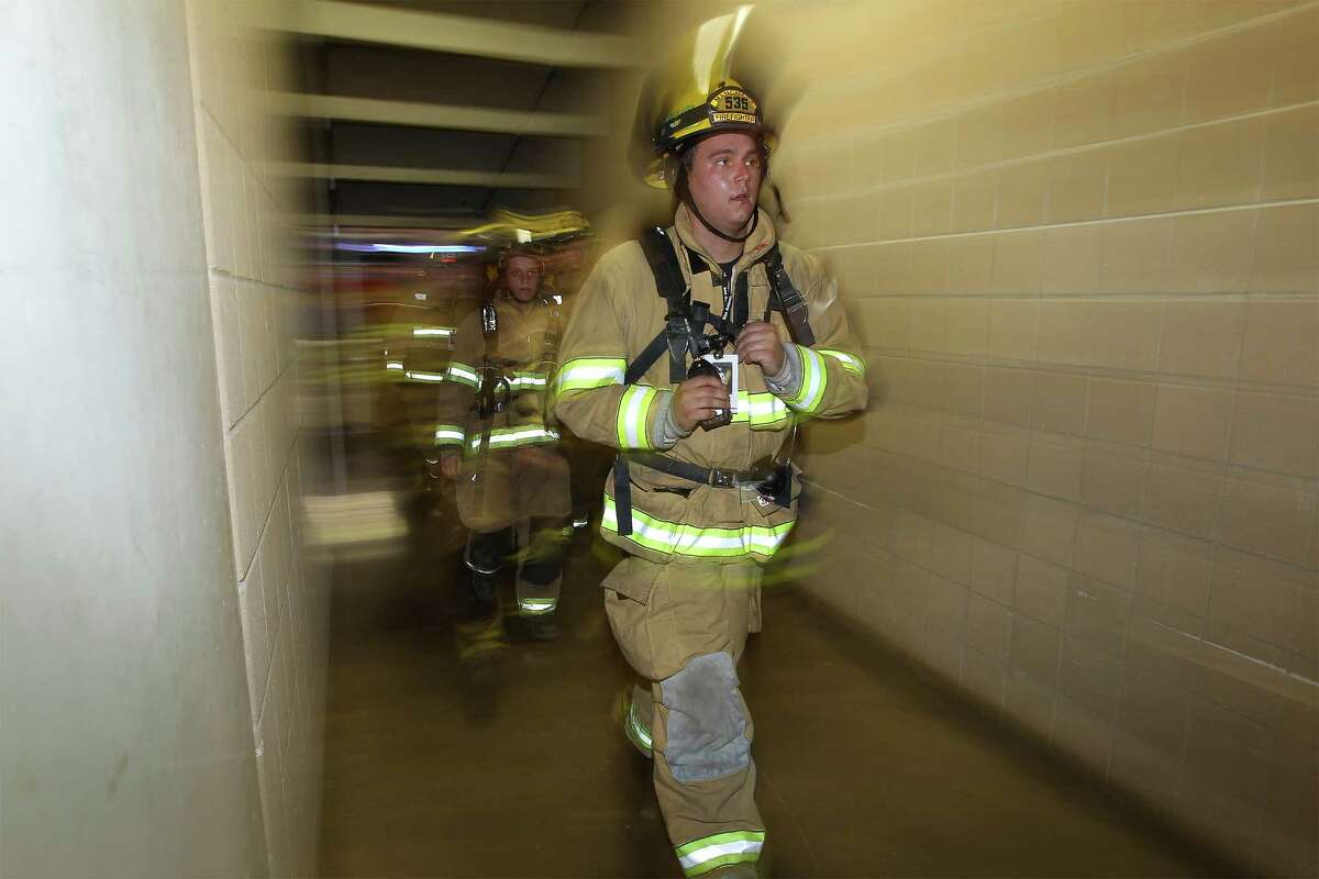 Firefighters exit a tunnel inside the Alamodome during the San Antonio 110 9/11 Memorial Climb at the Alamodome on Thursday, Sept. 11, 2014. Hundreds of first responders and civilians gathered to take part in the event to pay tribute to the fallen firefighters from Sept. 11, 2001. Each participating first responder carried the face and name of firefighter that perished 13 years ago in New York City. Many wore bunker gear and breathing apparatus that added up to additional pounds as a tribute during their climb. At the end of the climb, a name tag of the fallen firefighter was placed on a 9/11 memorial, their name called out and a bell was rung.