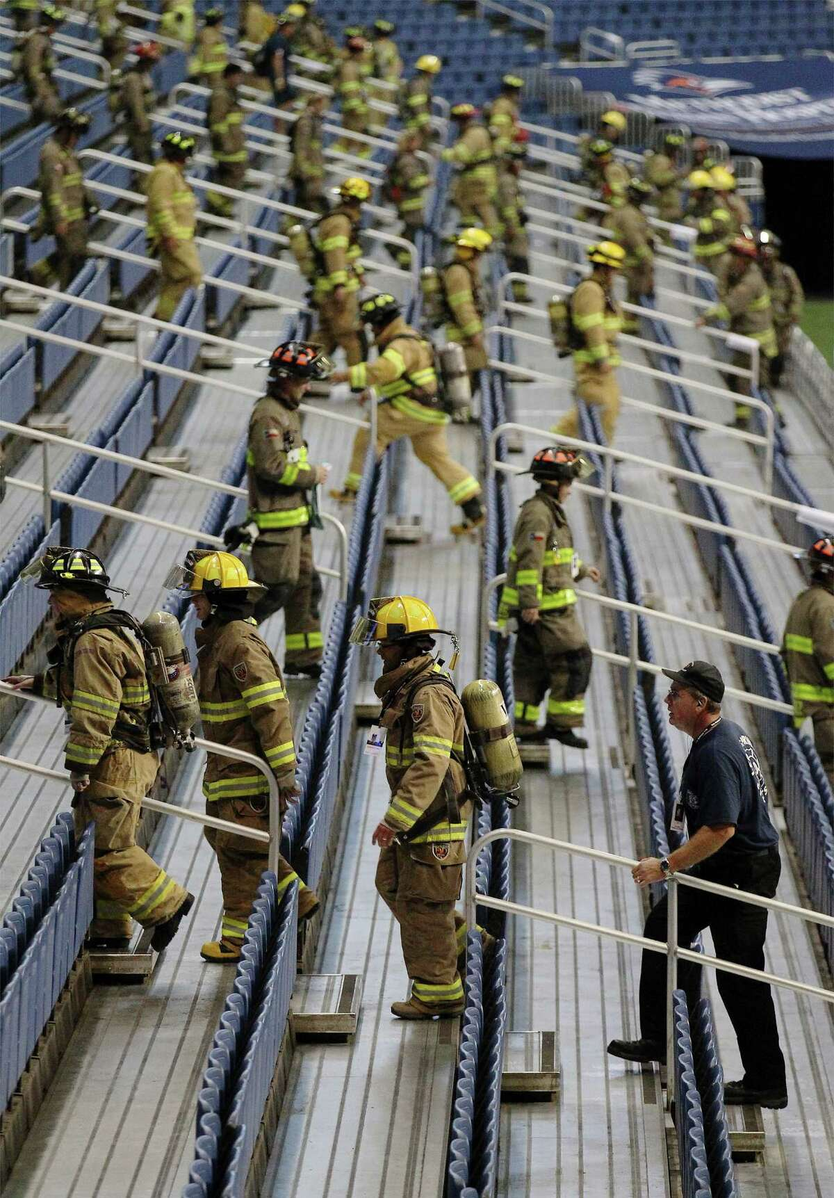 Firefighters climb the steps inside the Alamodome during the San Antonio 110 9/11 Memorial Climb at the Alamodome on Thursday, Sept. 11, 2014. Hundreds of first responders and civilians gathered to take part in the event to pay tribute to the fallen firefighters from Sept. 11, 2001. Each participating first responder carried the face and name of firefighter that perished 13 years ago in New York City. Many wore bunker gear and breathing apparatus that added up to additional pounds as a tribute during their climb. At the end of the climb, a name tag of the fallen firefighter was placed on a 9/11 memorial, their name called out and a bell was rung.