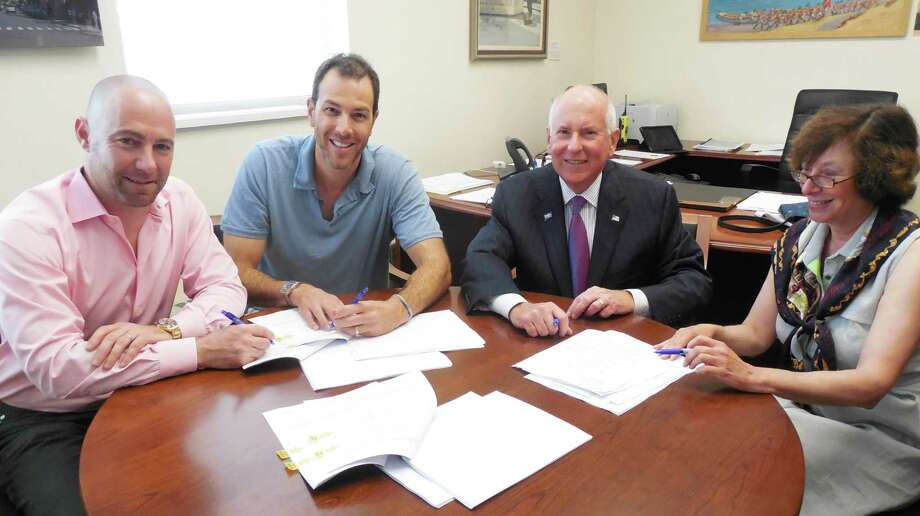 From left: Dan Zelson and David Waldman, partners in the Bedford Square and Kemper-Gunn LLC projects, First Selectman Jim Marpe and Selectman Helen Garten sign a ground lease Thursday morning for the relocation of the historic Kemper-Gunn house from Church Lane to the town-owned Baldwin parking lot. Photo: Anne M. Amato / westport news