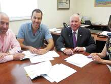 From left: Dan Zelson and David Waldman, partners in the Bedford Square and Kemper-Gunn LLC projects, First Selectman Jim Marpe and Selectman Helen Garten sign a ground lease Thursday morning for the relocation of the historic Kemper-Gunn house from Church Lane to the town-owned Baldwin parking lot.