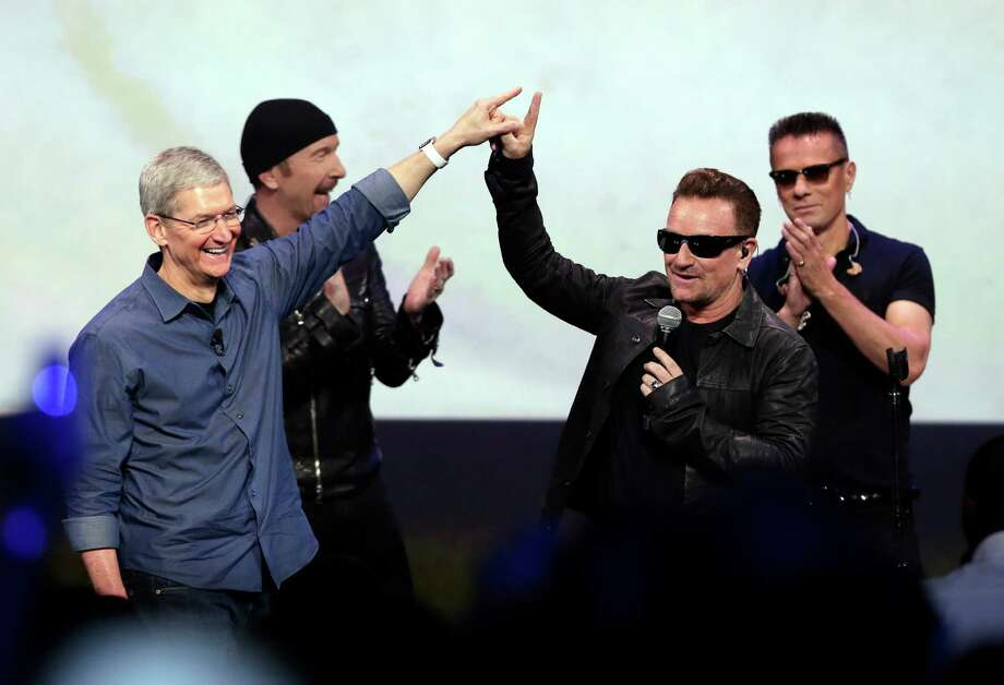 Apple CEO Tim Cook (left) greets Bono after the band U2 performed at the end of the Apple event Tuesday. Photo: Marcio Jose Sanchez, STF / Associated Press / AP