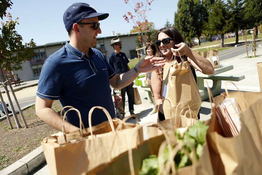 Peter Koshland gets his Farmigo items from PTA volunteer Rebecca Matthews at Malcolm X Elementary School in Berkeley. Photo: Scott Strazzante, The Chronicle