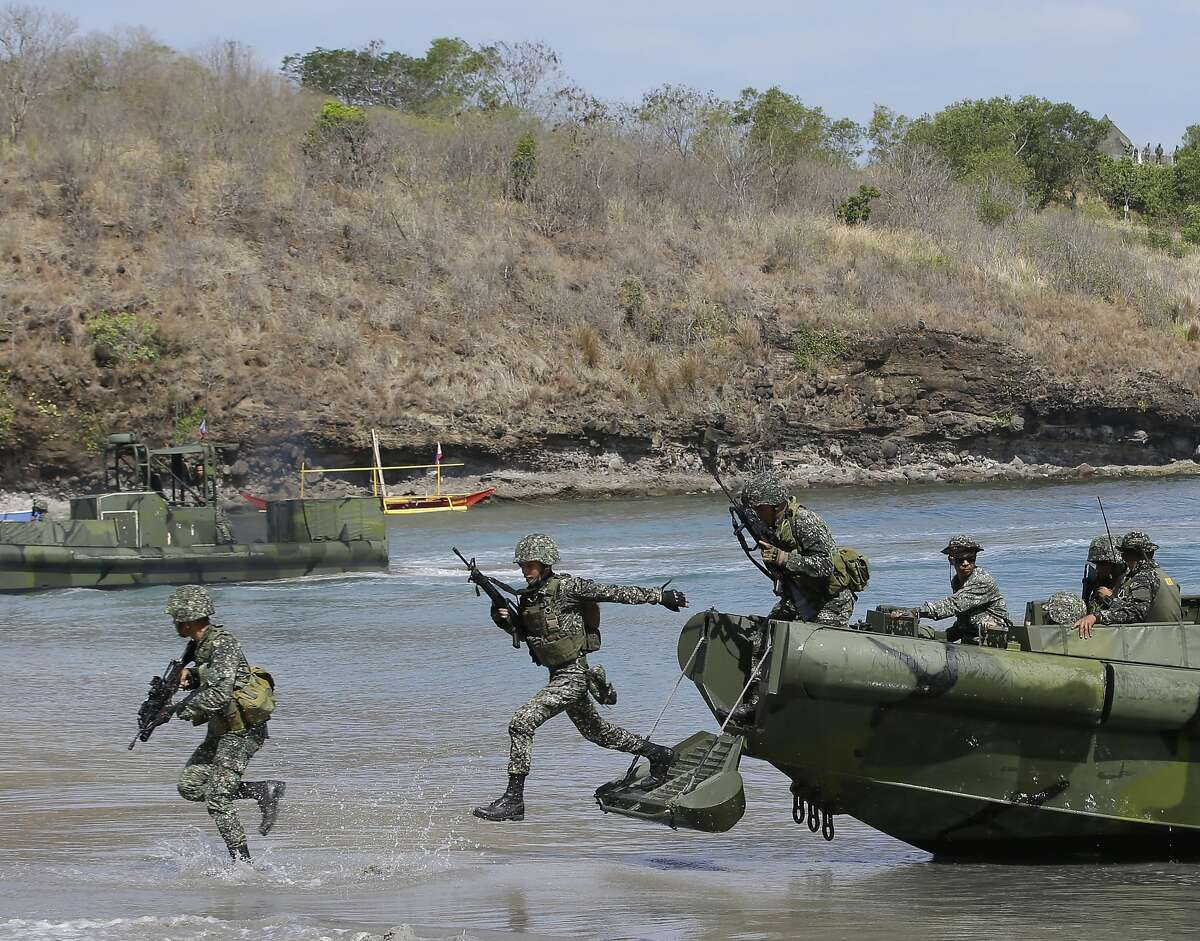 FILE - In this May 11, 2014 file photo, Philippine Marines exit from a U.S.-made fast craft as they assault a target during a live-fire joint U.S.-Philippines military exercise dubbed Balikatan 2014 at the Philippine Marine base at Ternate township, Cavite province south of Manila, Philippines. Several Asian nations are arming up, their wary eyes fixed squarely on one country: a resurgent China that's boldly asserting its territorial claims all along the East Asian coast. The scramble to spend more defense dollars comes amid spats with China over contested reefs and waters. Other Asian countries such as India and South Korea are quickly modernizing their forces, although their disputes with China have stayed largely at the diplomatic level. (AP Photo/Bullit Marquez, File)
