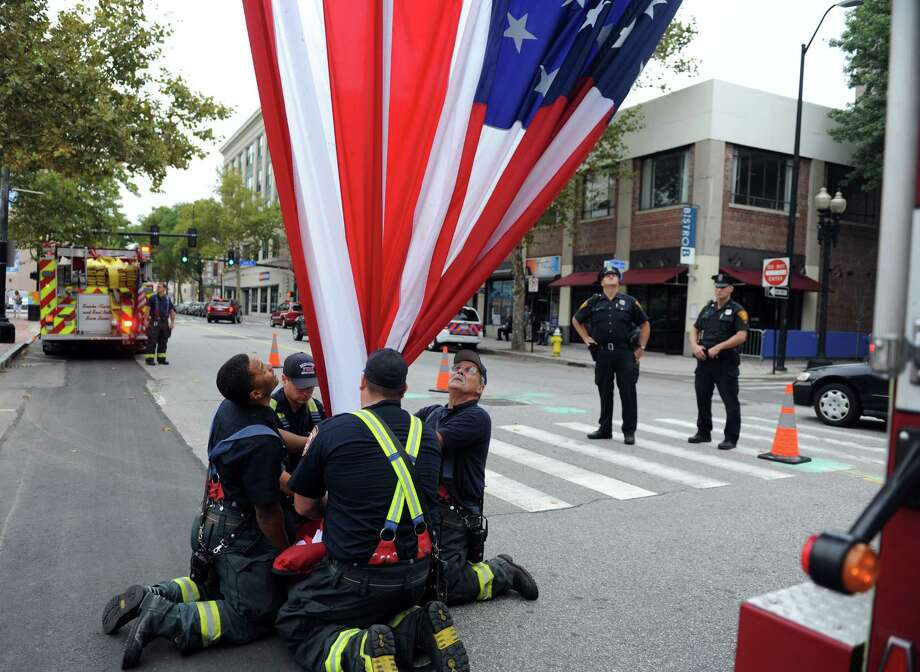 Bridgeport firefighters fold up the American flag following a 9/11 remembrance ceremony Thursday, Sept. 11, 2014 outside the Margaret E. Morton Government Center in Bridgeport, Conn. Photo: Autumn Driscoll / Connecticut Post
