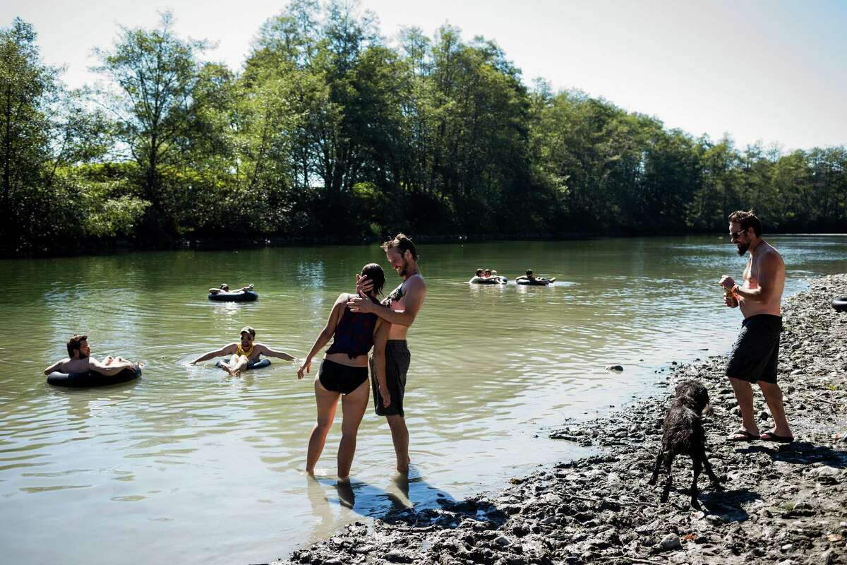 Campers relax by the river at the eighth annual Lo-Fi Festival Sunday, Sept. 7, 2014, at The Smoke Farm in Arlington.