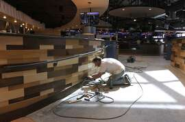 Adam Fencil nails wood planks to a wall at the new Plank beer garden and bowling alley in Oakland, Calif. on Thursday, Sept. 11, 2014. The family entertainment center is scheduled to open in October in the site of the old Barnes and Noble bookstore at Jack London Square.