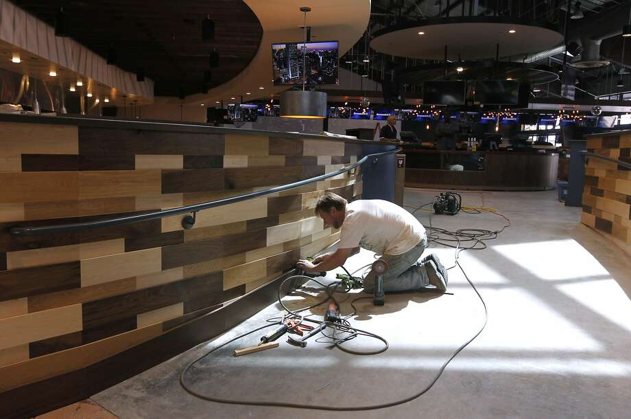 Adam Fencil works on the interior of Plank, which is scheduled to open next month in Jack London Square. Photo: Paul Chinn, The Chronicle