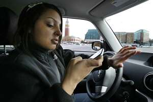 New driver Brandi Eadie, 16, reads a text as she drives through a rubber-cone course in Seattle to demonstrate the dangers of phone use while driving. A reader comments on the practice.
