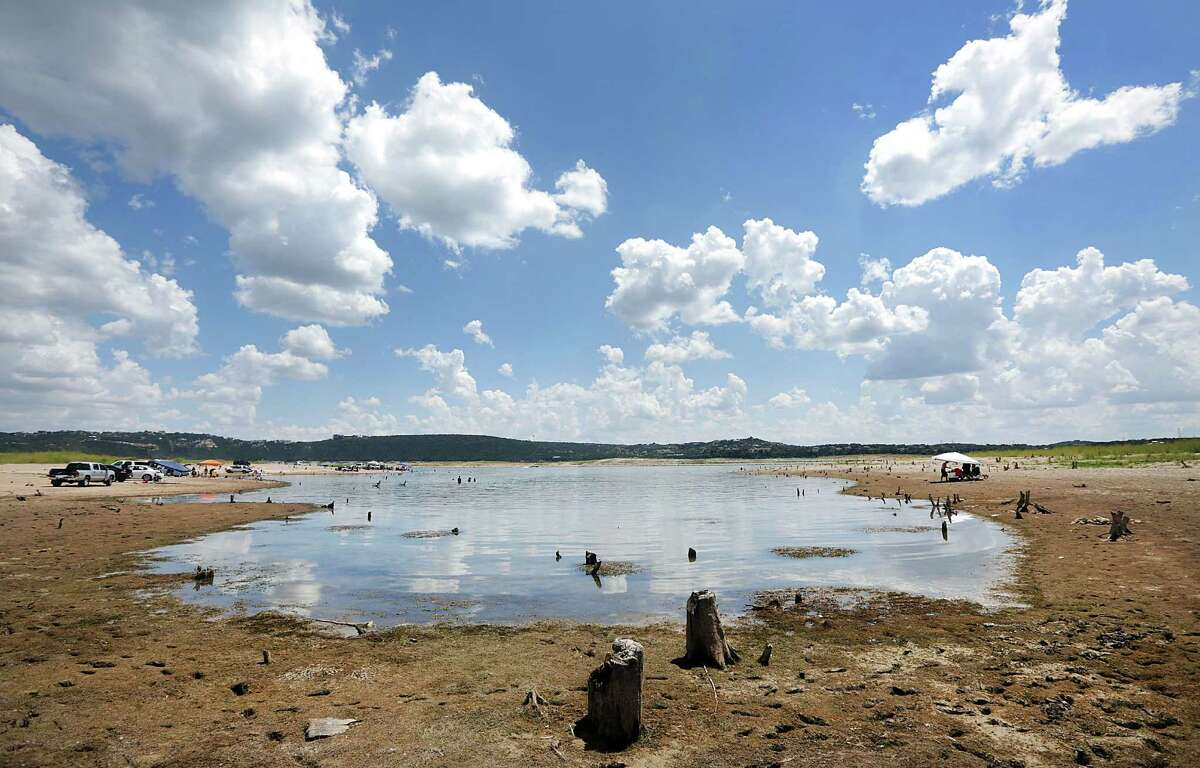 Tree stumps stick out of dried-up Lake Travis last year, one sign of the type of extreme weather that is a hallmark of climate change.
