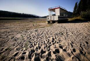 An abandoned pontoon boat sits on dry land which would typically be filled with water along the shore at Bass Lake on Friday July 18, 2014, near Oakhurst, Calif. A prolonged drought could make it harder -- and more expensive -- for California to cut its greenhouse gas emissions and fight global warming. Drought cuts the amount of electricity that California gets from hydroelectric dams. To compensate, the state has to rely more on power plants burning natural gas.