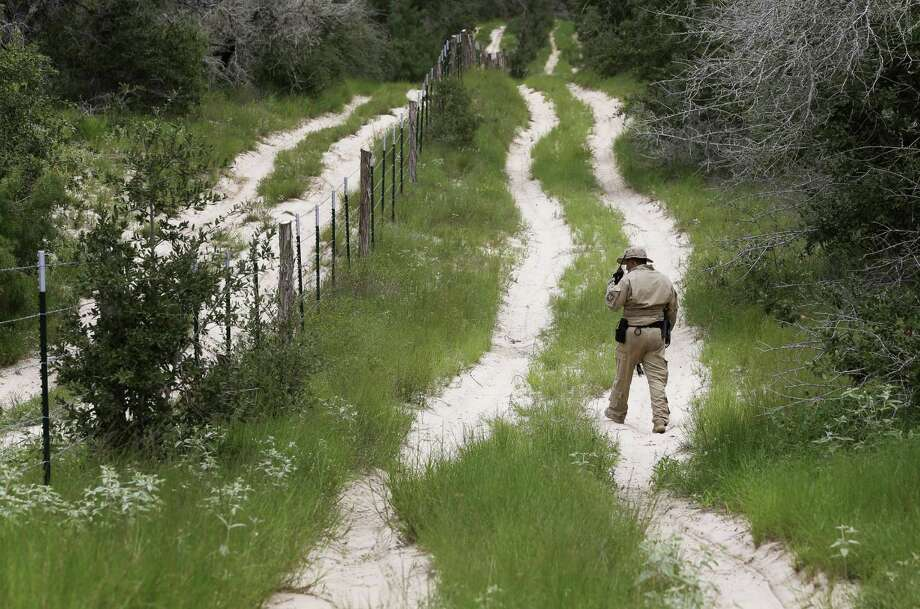 A U.S. Customs and Border Protection agent looks for signs along a trail while on patrol near the Texas-Mexico border. Photo: Associated Press / AP