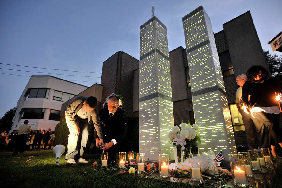 Ted Jankowski, director of Public Safety, Health and Welfare, lights a candle with his son, Thomas, at the World Trade Center Memorial following the annual Sept. 11 terrorist attack remembrance ceremony at the Woodside Fire House on Washington Boulevard in Stamford, Conn., on Thursday, Sept. 11, 2014. Photo: Jason Rearick / Stamford Advocate