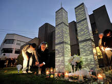 Ted Jankowski, director of Public Safety, Health and Welfare, lights a candle with his son, Thomas, at the World Trade Center Memorial following the annual Sept. 11 terrorist attack remembrance ceremony at the Woodside Fire House on Washington Boulevard in Stamford, Conn., on Thursday, Sept. 11, 2014.