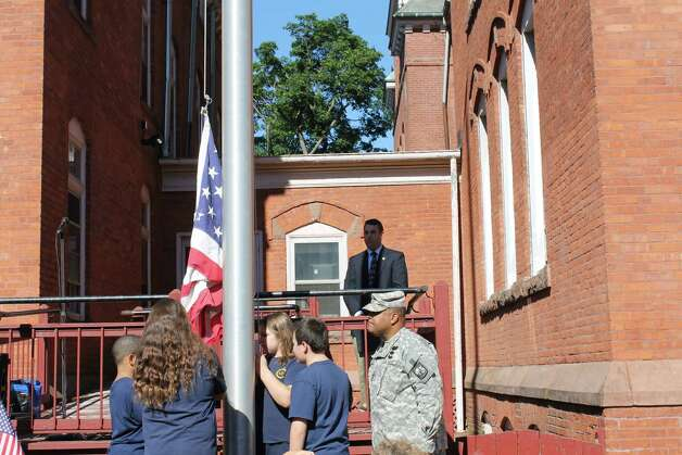 St. Augustine's School in Lansingburgh welcomed Heath Blackmon from Siena College's ROTC department into the school for a flag-raising ceremony on Monday, Sept. 8. Here, Tavon Lockridge, Raegan McGowan, Breanna Sweener and Connor O'Brien follow commands from Blackmon.