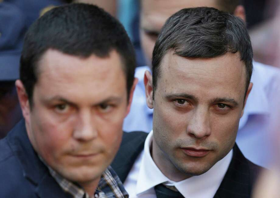 Oscar Pistorius, right, accompanied by a relative leaves the high court in Pretoria, South Africa, Thursday, Sept. 11, 2014. Presiding Judge Thokozile Masipa is expected to announce her verdict in Pistorius' murder trail after scrutinizing evidence Thursday and Friday given by 37 witnesses in a court transcript running to thousands of pages in a drama that has played out over six months. (AP Photo/Themba Hadebe) Photo: Themba Hadebe, STF / AP
