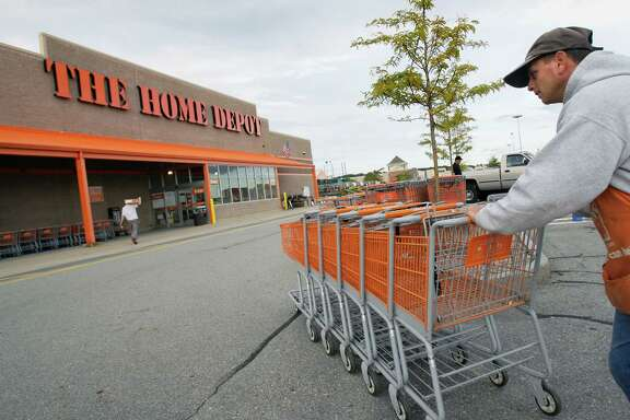 FILE - In this file photo made Oct. 6, 2009, employee John Abou Nasr pushes shopping carts in the parking lot of a Home Depot in Methuen, Mass. Home Depot's data breach could wind up being among the largest ever for a retailer, but that may not matter to its millions of customers. (AP Photo/Elise Amendola, File)