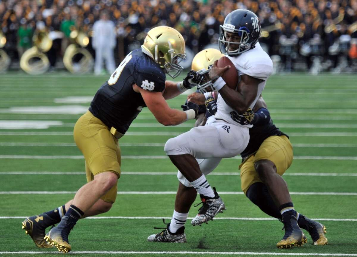Rice quarterback Driphus Jackson, front right, is tackled by Notre Dame linebackers Joe Schmidt, left, and Jaylon Smith during an NCAA college football game in South Bend, Ind., Saturday, Aug. 30, 2014. (AP Photo/Joe Raymond)